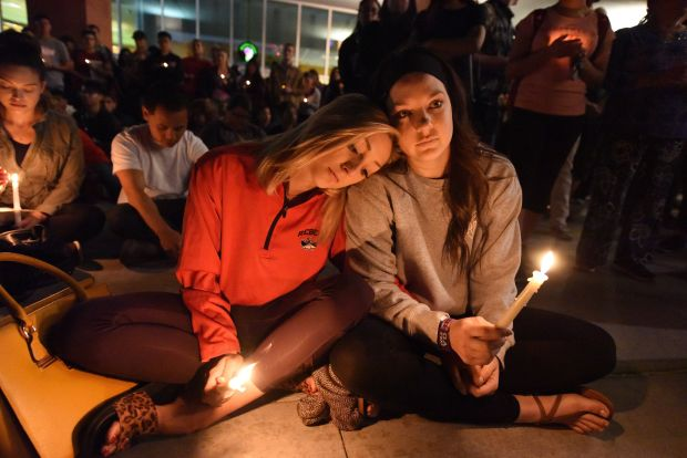 Lindsay Cotterman (L) and Shawna Pieruschka attend a candlelight vigil at the University of Las Vegas student union October 2, 2017, after a gunman killed at least 58 people and wounded more than 500 others when he opened fire on a country music concert in Las Vegas, Nevada late October 1, 2017.
