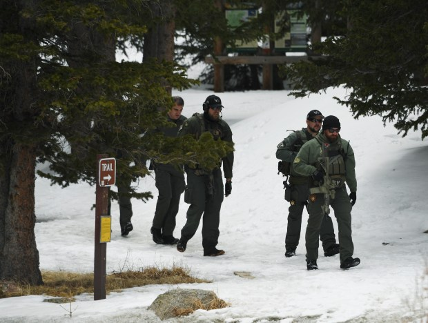 Swat officers walk out of the woods