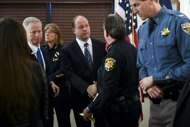 Colorado governor Jared Polis (L), shakes ...