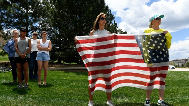 People hold an American flag as ...