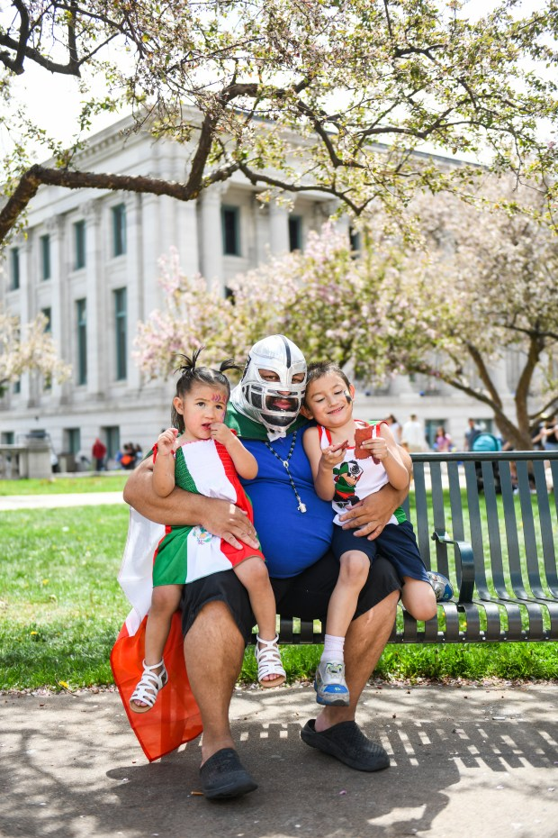 A man in a mask poses with his kids on Cinco de Mayo