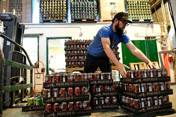 Production assistant Aaron Colburn stacks beer ...