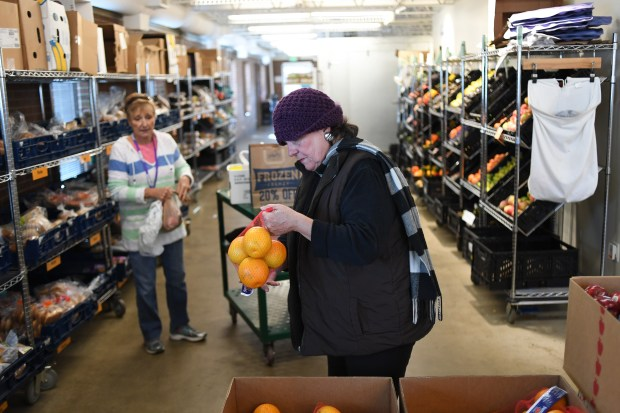 Carolyn Antel, center, picks out groceries, ...