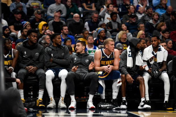 The Denver Nuggets bench watches the ...