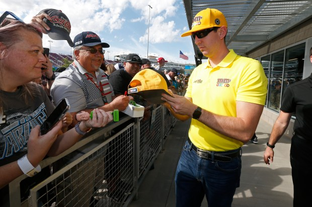 Driver Kyle Busch, right, gives autographs ...