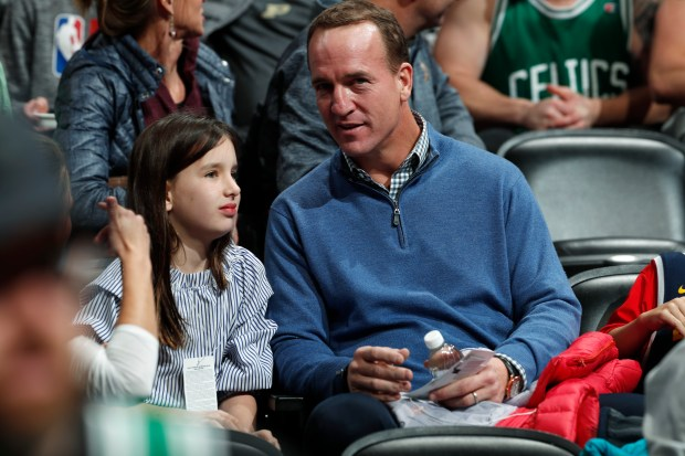 Retired NFL quarterback Peyton Manning, right, ...