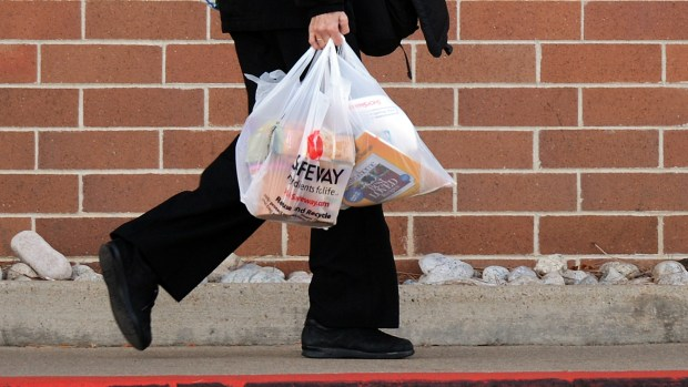 A shopper carries out groceries, Monday ...