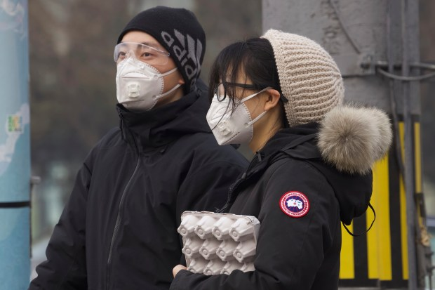 Residents wearing masks wait at a ...
