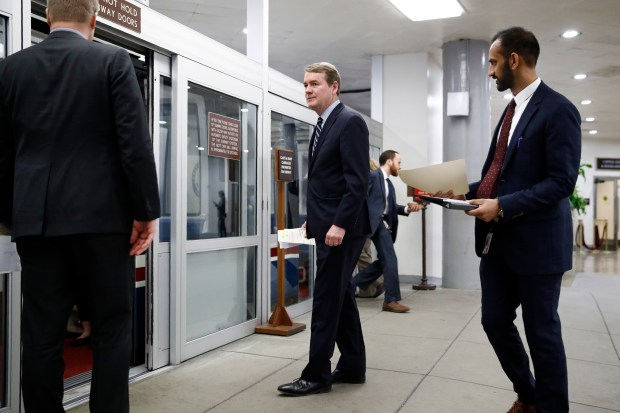 Sen. Michael Bennet, D-Colo., center, walks ...