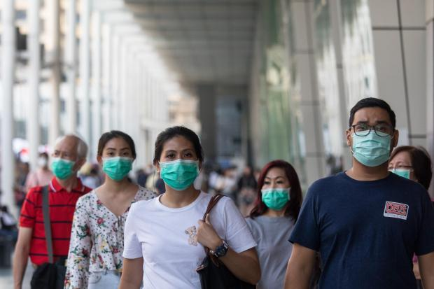 Pedestrians wear face masks in Bangkok, ...