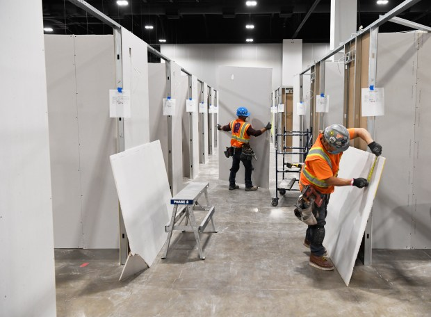 Construction workers measure and put drywall ...