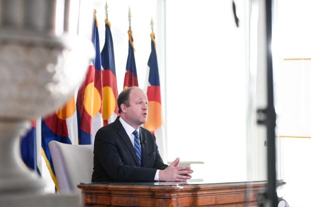 Colorado Governor Jared Polis delivers an ...