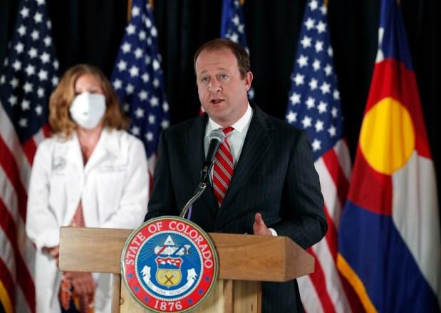 Colorado Governor Jared Polis, right, makes ...