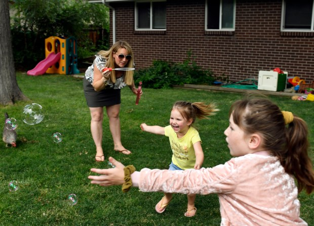 Brittany Nidy, left, blows bubbles for ...