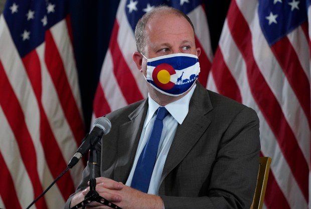 Colorado Governor Jared Polis wears a ...