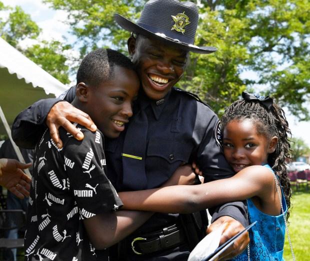 Denver Sheriff's Deputy Eastman ZayZay, center, class of 2021-1, gets a congratulatory hugs from his kids