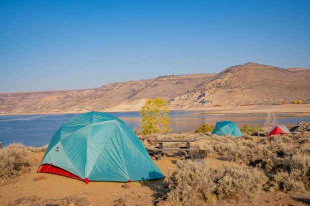 A tent sits on a campground near a lake