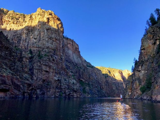 A view of a canyon with dark walls, a river and blue sky