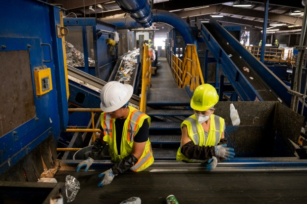 Employees sort through plastic recyclables at ...