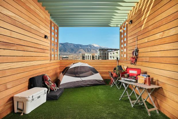 Campers set up a tent, their camp stove and cooler on the camping platform - with a view of Pikes Peak - at Kinship Landing, a hotel in downtown Colorado Springs.