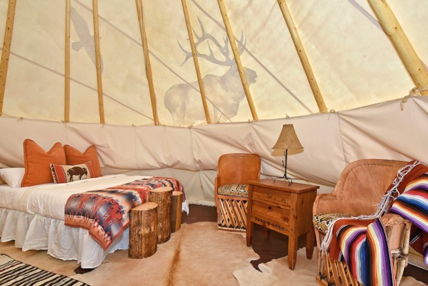 A roomy tepee at Puma Hills at Lake George includes a large bed with thick mattress, rugs on the floors, a sitting area and electricity.