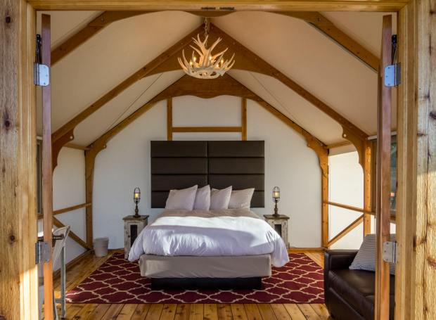A luxury canvas-sided tent at the Royal Gorge Cabins at the Royal Gorge features many hotel-like comforts - thick mattresses, lighting, a sitting area, wooden floors and more.