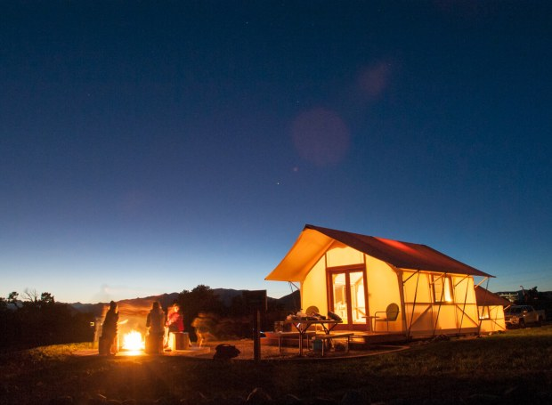 Guests sit around a private fire ring outside a glamping tent at the Royal Gorge Cabins at the Royal Gorge near Canon City.