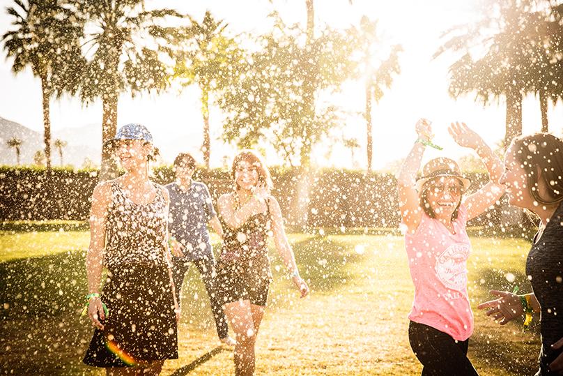 The Visit California press trip cools off in a sprinkler at Safari Camp in Coachella, California, April 21, 2016.