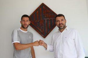 Raúl Campos y José Tirado se dan el puño con el escudo del Palma Futsal detrás (sin mascarilla)