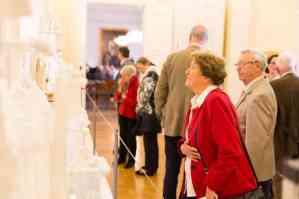 Ausstellungsbesucher betrachten Taufkleider-Galerie. Foto: Schlossmuseum/Marek Kruszewski