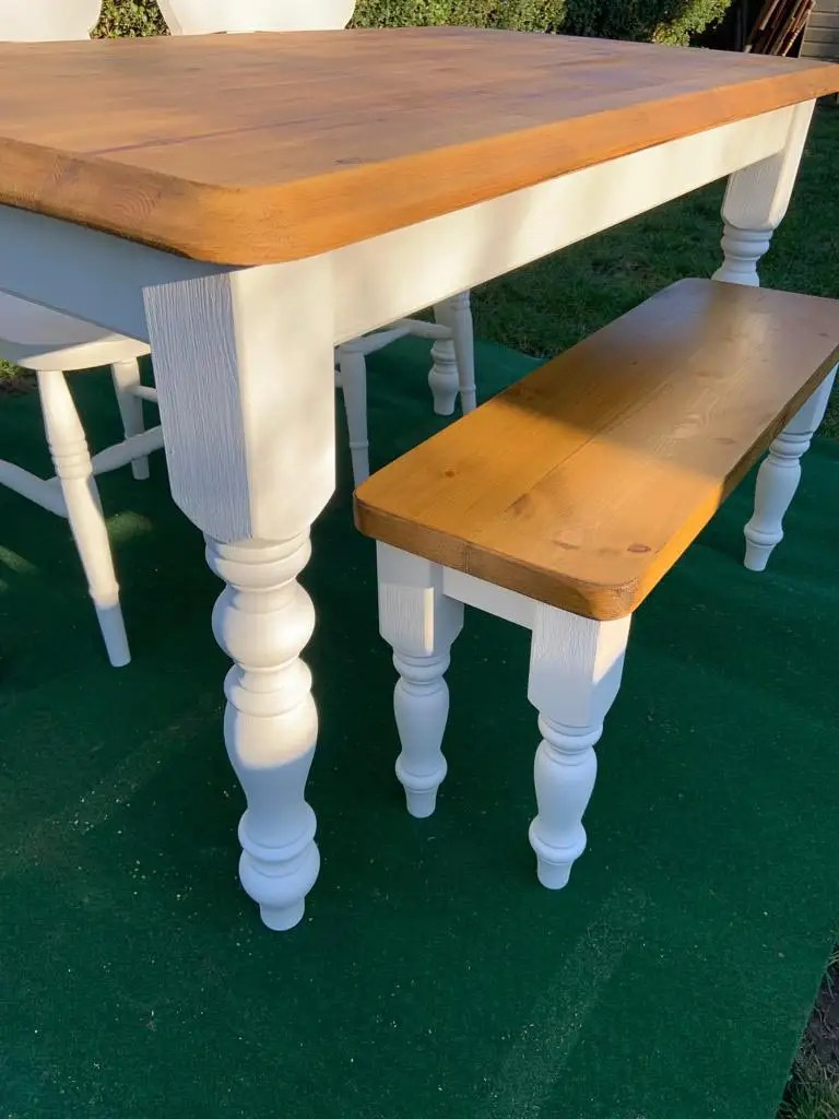 white dining room table and bench with stained wooden top