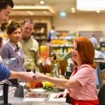 Kundschaft beim bezahlen an der Kasse im Supermarkt