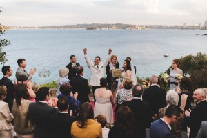 The groom throws his arms up after a successful wedding ceremony