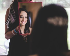 The bride has a peek at her makeup before the big day