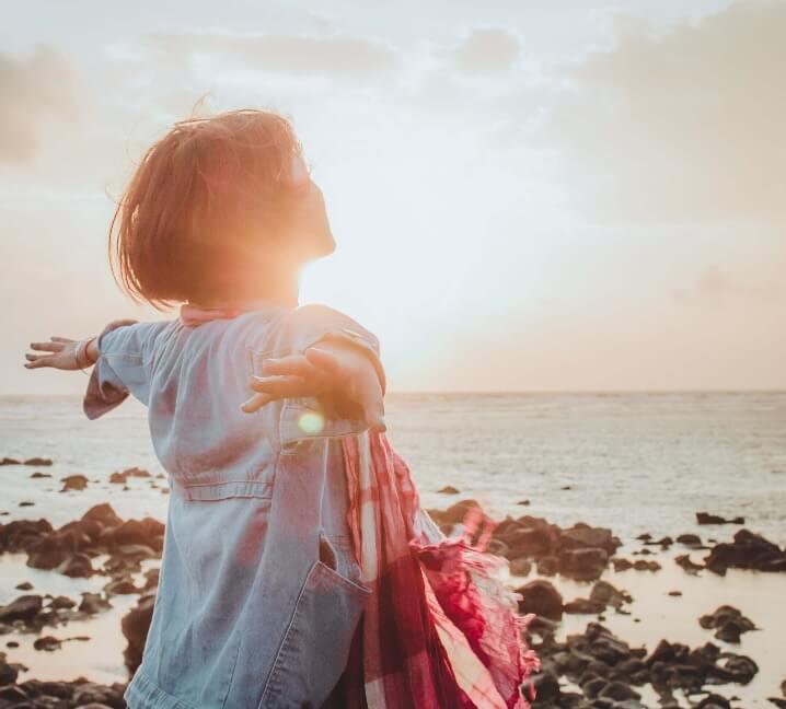 Frau am Strand im Sonnenuntergang