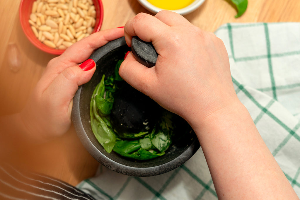 Acrescentando as folhas de manjericão e uma pitada de sal