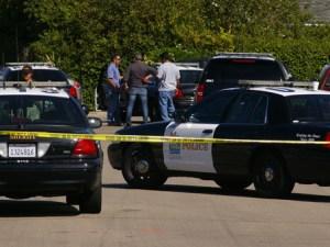 Carros de policía en escena del crimen acordonada