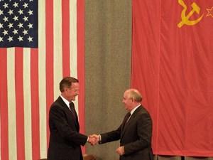 Mijail Gorbachov con bandera rusa y estadounidense al fondo