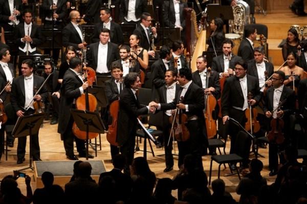 El director Dudamel felicita a la primera viola, Ismel Campos, luego del segundo concierto en el centro cultural Bozar. Foto FundaMusical Simón Bolívar