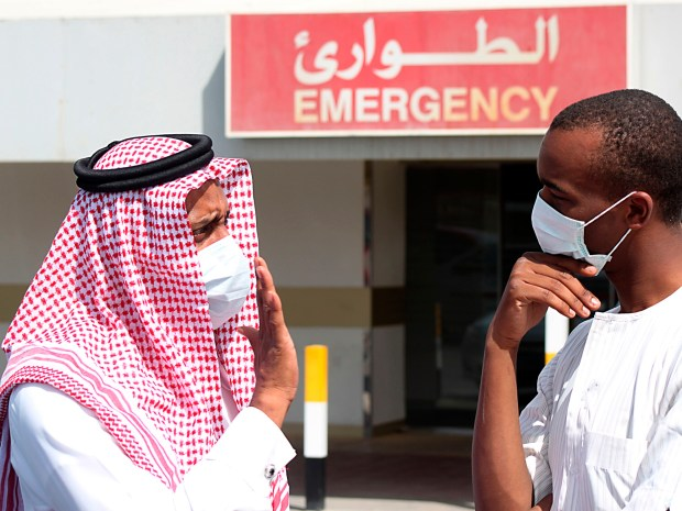 Men wearing surgical masks as a precautionary measure against the novel coronavirus, speak at a hospital in Khobar city in Dammam