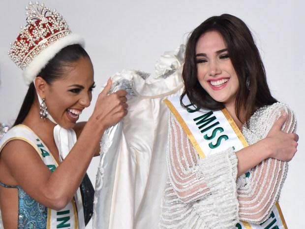 Miss Venezuela Edymar Martinez (R) is congratulated by Miss Internati