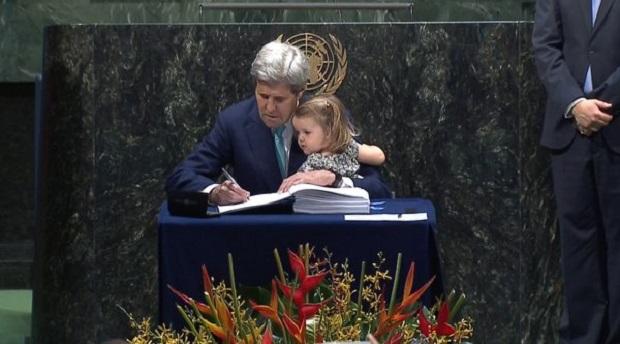 John Kerry, Secretario de Estado de EEUU, firma con su nieta en brazos el Acuerdo