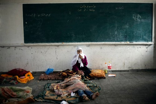 Palestinian woman, who fled her house following an Israeli ground offensive, stays at a United Nations-run school in Rafah in the southern Gaza Strip