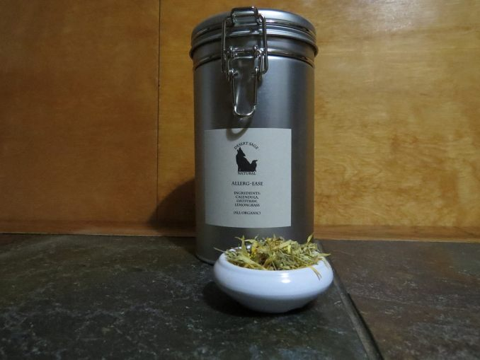 """A large cylindrical tea tin, with a latching mechanism for closure, labeled """"Allerg-Ease""""  In front of the tin is a small white bowl filled with bits of Calendula flowers and other herbs."""