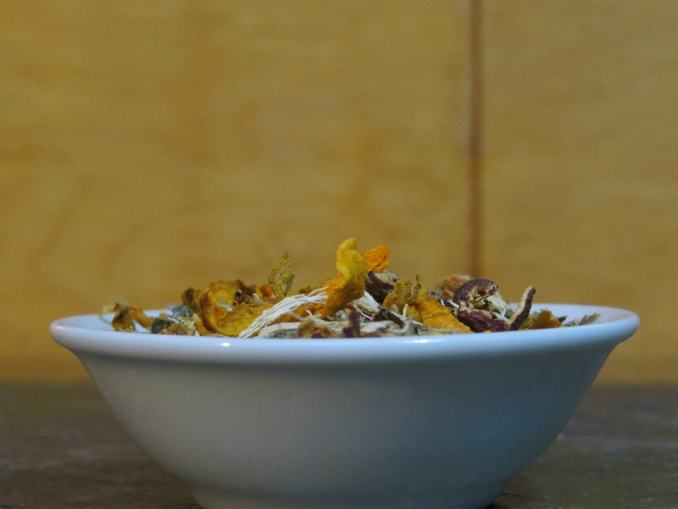 Closeup shot of a small white bowl. Peeking up over the edge you can see a blend of meadosweet, Turmeric Root, Hawthorn berries, Dandelion Root, and Yucca.