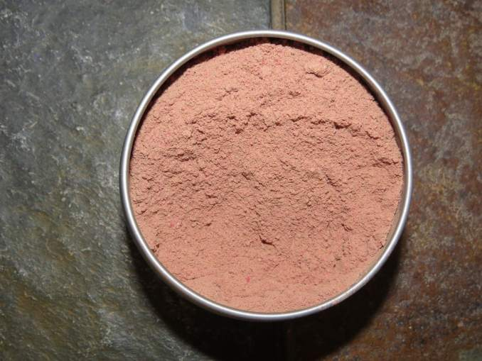 Pomegranate Cocoa Powder in a metal tin, on stone, shot from above