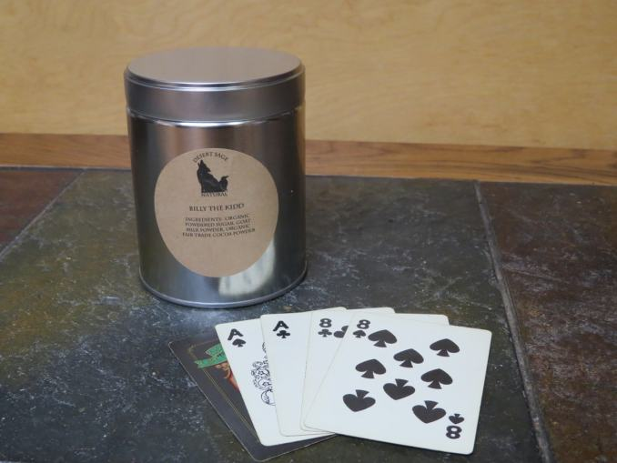 Labeled Tin of Billy the Kidd Cocoa with Aces and Eights Hand in Front of it.
