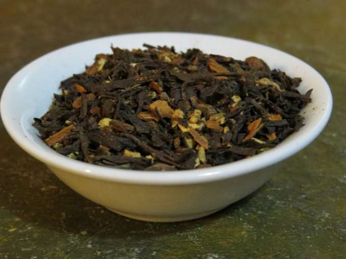 Small white bowl of caravan tea and chai spices on a marble stone background