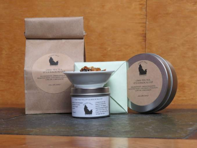 """A bag, small metal tin, origami square, and medium metal tin all labeled """"Chai Tea Tea, It's a magical cup"""" with the ingredients list of the tea. Atop the small tin is a white bowl with the tea blend in it."""