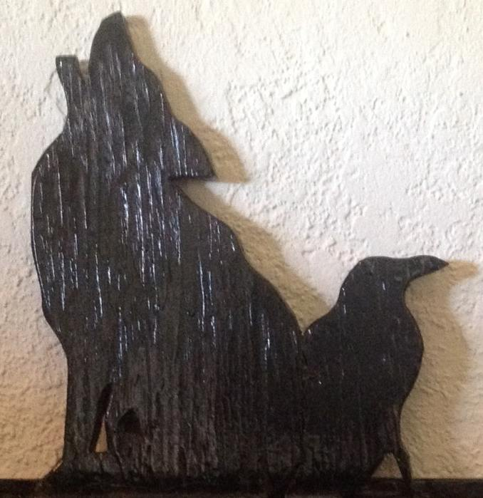 A carved silhouette of a Raven and a Coyote